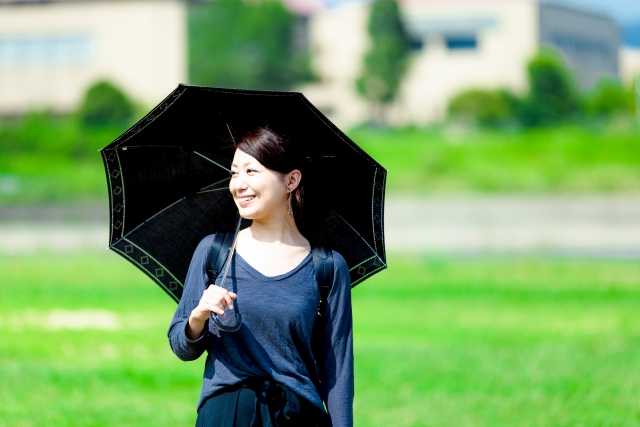 黒い日傘をさす女性